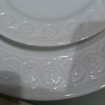 White china plate with border of curling lines